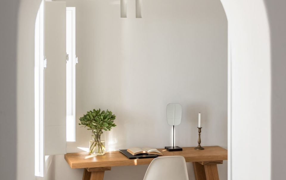 Desk with a book, plant, and lamp
