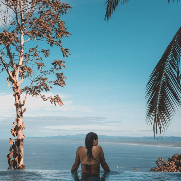 Woman in an infinity pool looking at the sea